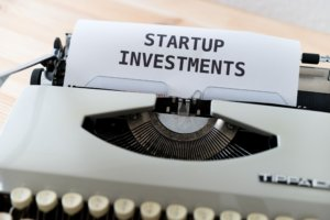 typewriter with paper coming out of it with the words startup investment on the paper