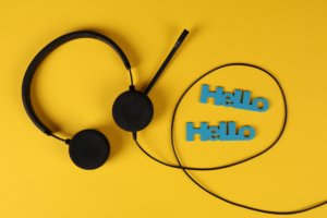 black headset on yellow background with the words hello, hello in blue